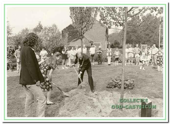 Burgemeester Schouwenaar helpt mee en geeft een officieel tintje aan het planten van een vrijheidsboom.