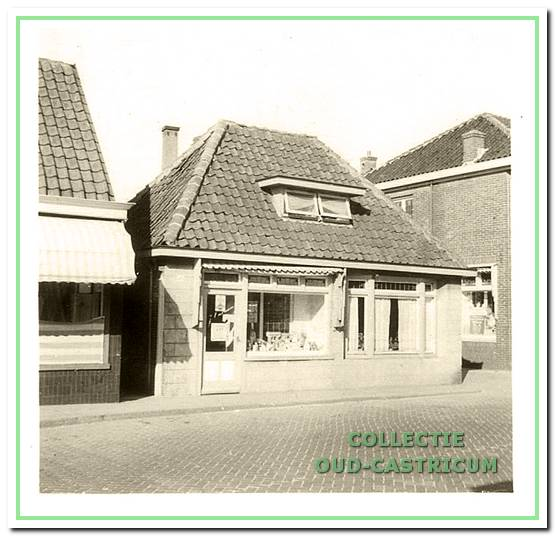 De winkel van Jan Castricum, Dorpsstraat 48, omstreeks 1950. De voorgevel werd in 1939 vernieuwd na ernstig te zijn beschadigd door een uit de bocht gevlogen vrachtwagen. Links een glimp van de manufacturenzaak van Twisk. Rechts de zijgevel van het pand van bakker Gerard Hemmer.