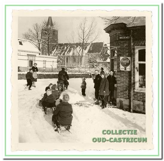 Op de hoek Schoolstraat - Breedeweg, waar Jan Dekker na een stevige sneeuwbui een aantal sleetjes aan zijn motor op sleeptouw nam.