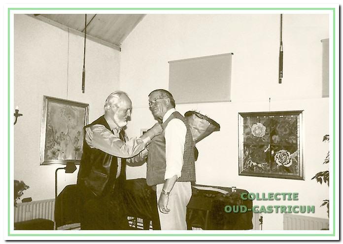 Thijs Geerts (rechts), van 1962 tot 1992 regisseur bij Pancratius, krijgt door Bertus Stuifbergen de gouden speld met diamant opgespeld in november 2002.