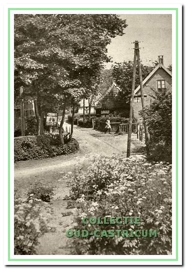 Een kijkje vanaf het pad naar de ziekenbarak de Kramersweg in. Links is een reclamebord te zien van Piet Bakker, de gistboer en in het eerste huis rechts vinden we het winkeltje van Jaap Stuifbergen. Naast dat huis liep het Onderlangs en er tegenover kwam het Slingerpad op de Kramersweg uit.