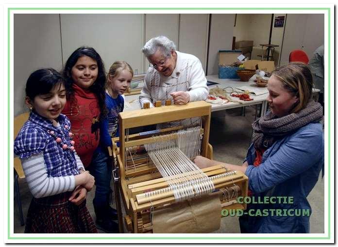 Oude ambachten. Tijdens een educatieproject in 2013 laat werkgroeplid Anneke van der Kamp de kinderen zien hoe er op een weefgetouw werd gewerkt.