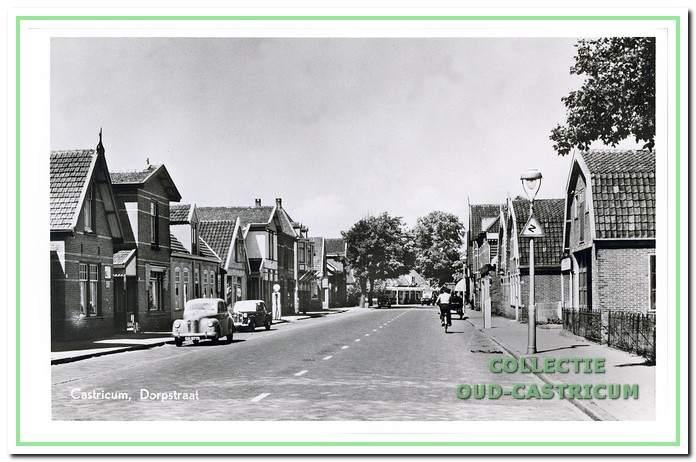 Doorkijk Dorpsstraat in 1952 met achtereenvolgens links de woonhuizen nr 16,18 (later café), 20 (later café), 22 (op achterterrein garagebedrijf, later bowlingbar), 24 en een bakkerswinkel op 26. Rechts de woonhuizen nr 23 (later kantoor), 25 en een pakhuis op 27.