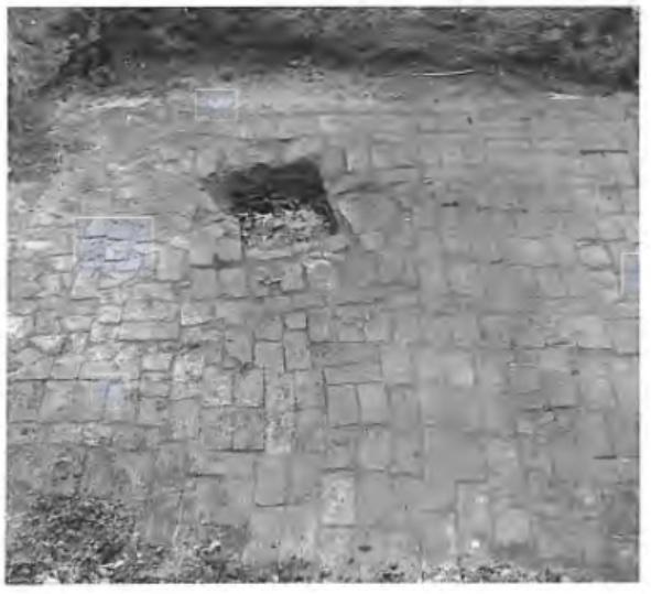 Het bakstenen vloertje met de uitsparing, waarschijnlijk om het schrobwater kwijt te kunnen.