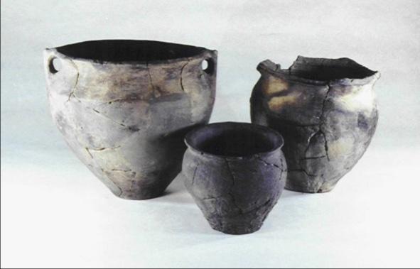 De drie gerestaureerde potten, afkomstig uit de afvalkuil. Links de pot met de knobbeloortjes, rechts de pot met breed uitgeknepen randdelen, vooraan het potje met de ruwe onderhelft.