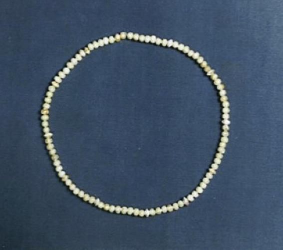 Kralenketting van glaspasta uit de 4e eeuw. De kralen hebben een hart van goudfolie. De ketting werd aangetroffen rand de hals van een op de buik begraven vrouw.