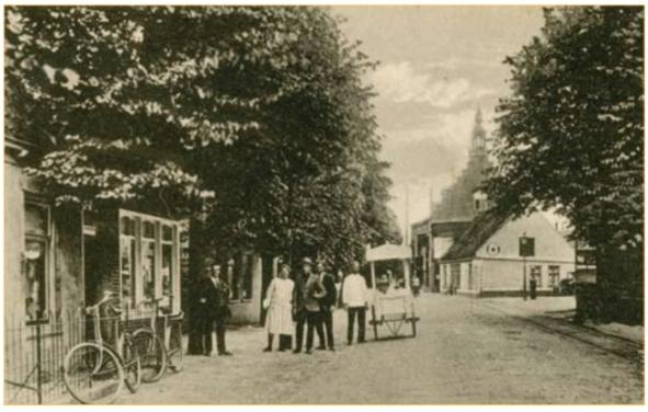 Foto uit 1919 met links de winkel van de familie Hogenstijn. De foto is mogelijk genomen ter gele- genheid van de opening van de winkel die in dat jaar plaatsvond. De personen voor de winkel zijn waarschijnlijk Marijtje Hogenstijn - Ineke met drie van haar zonen. Een ijscoman kwam de feestvreugde verhogen