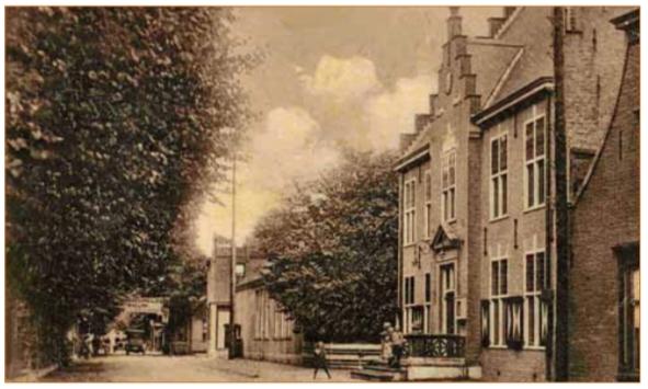 Het raadhuis met de oorspronkelijke luiken in 1928. De eerste lagere school stond er nog naast tot de sloop in 1934. Op de hoeken van het bordes zijn de 'stuiters' te zien.