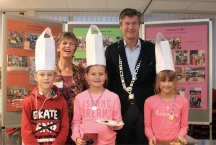 Burgemeester Mans met naast hem Pauline van Vliet en voor de winnaars van de bakwedstrijd