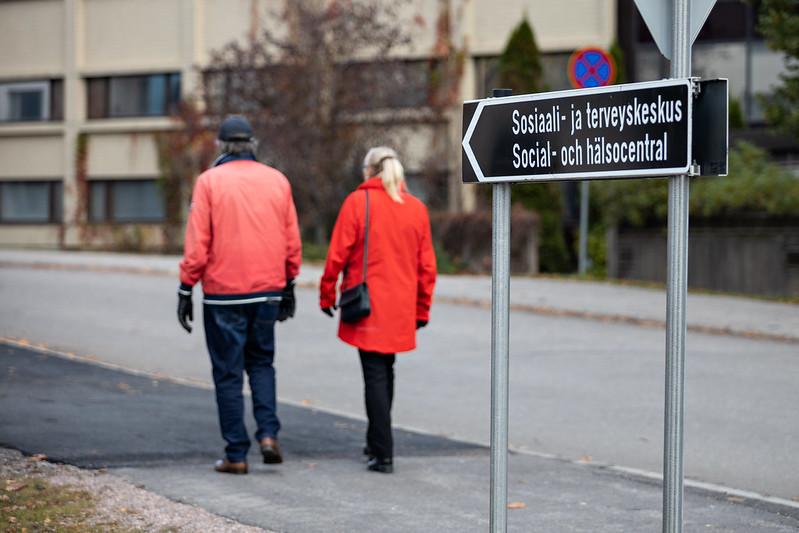 Kuvassa kaksi henkilöä kävelee sosiaali- ja terveyskeskuskyltin ohitse.