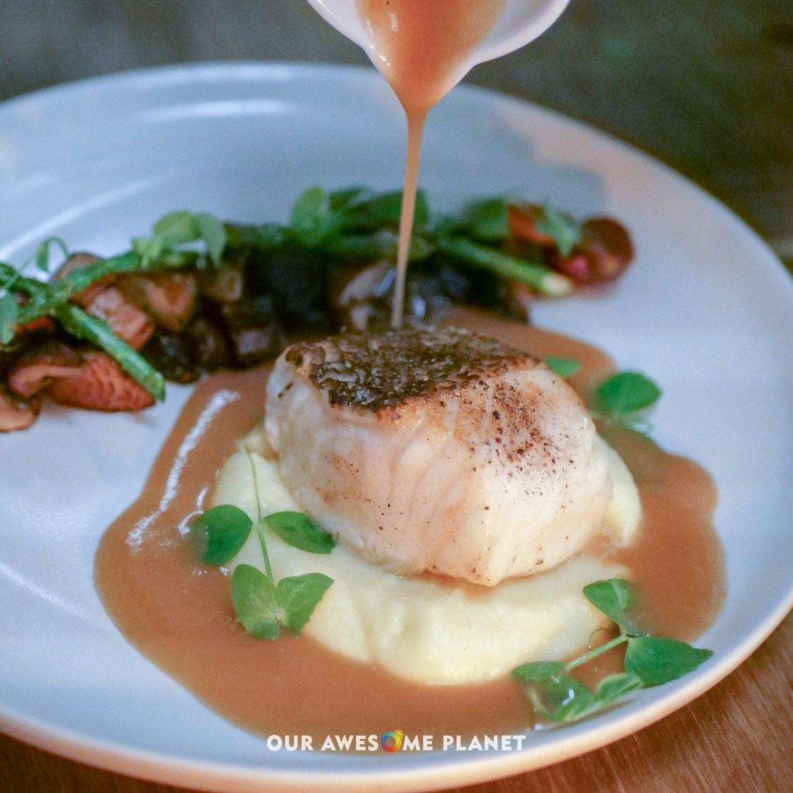 Seared Chilean Sea Bass (₱1,800). Shiitake mushrooms, garlic confit, Madeira-mushroom broth