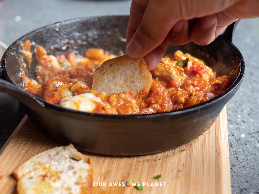 Shashuka (₱370). stewed tomatoes, baked eggs, ricotta, crostini