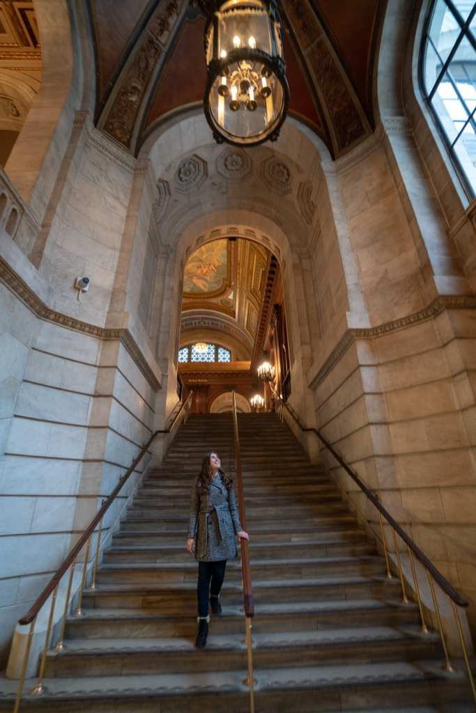 Kate walking down a stone staircase in the NYC Public Library, 5th Avenue branch. Kate is wearing a gray coat.