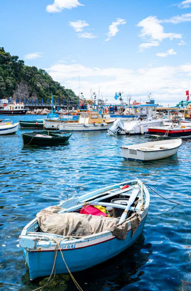Small fishing boat tied up near Sorrento, Italy. Other boats are in the background.
