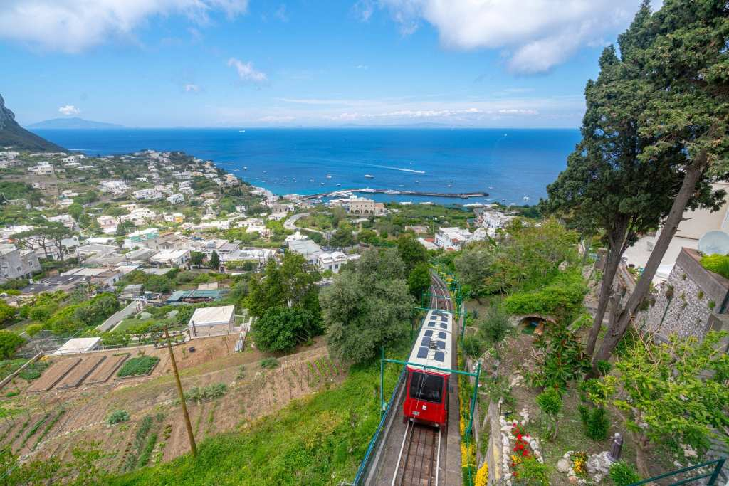 View of red funicular traveling up the hill to Capri Town