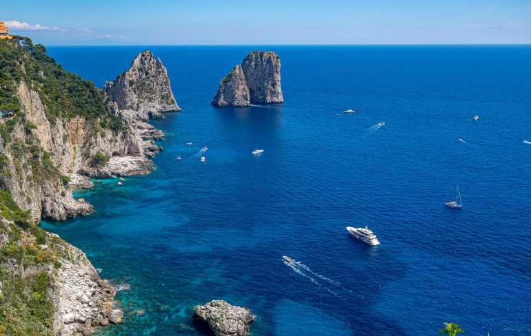 Photo of the Faraglioni of Capri taken from the Garden of Augustus. There are boats in front of the Faraglioni and the cliffs of Capri to the left.
