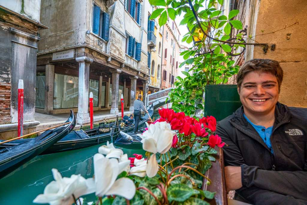 Man sitting in a restaurant along a Venetian canal. There's a flowerbox in the window next to him.
