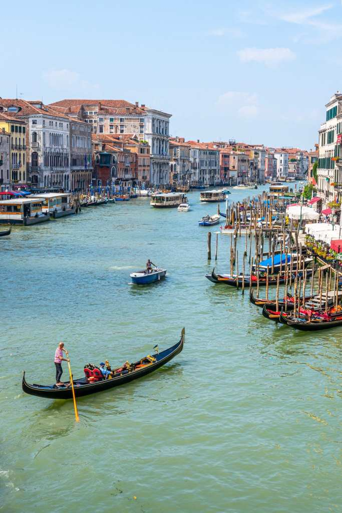 Venice Grand Canal with gondola paddling across it--a must-see item for your 2 week Italy itinerary!