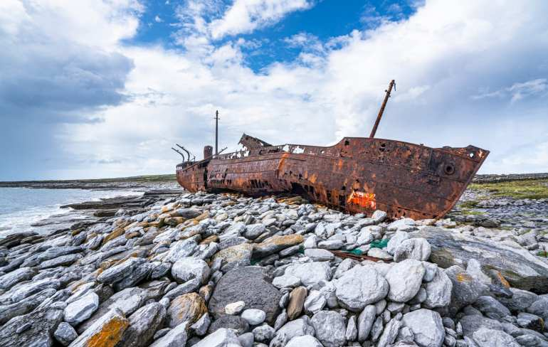Rusted Plassey Shipwreck laying on a stone beach on Inisheer Island Ireland, the smallest of the 3 Aran Islands