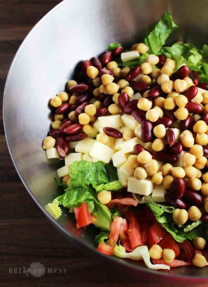 This southwestern chopped salad, with two kinds of beans, cubes of cheese, crunchy greens, and a tangy balsamic vinaigrette makes an easy weeknight meal.