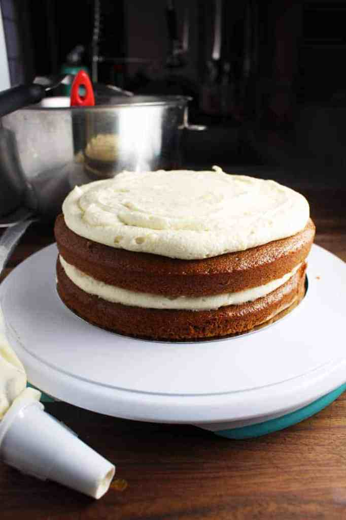 Two gingerbread cake layers stacked on a turntable with brown butter cream cheese frosting in progress