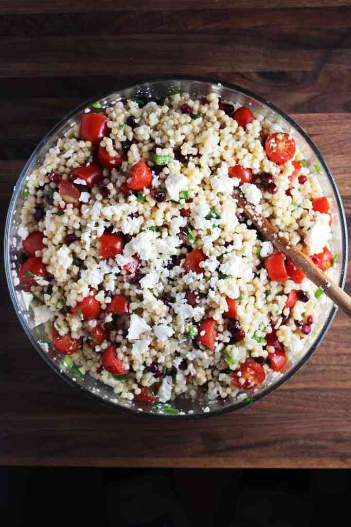 Overhead view of mediterranean Israeli couscous salad in a large bowl, tossed, with a wooden spoon