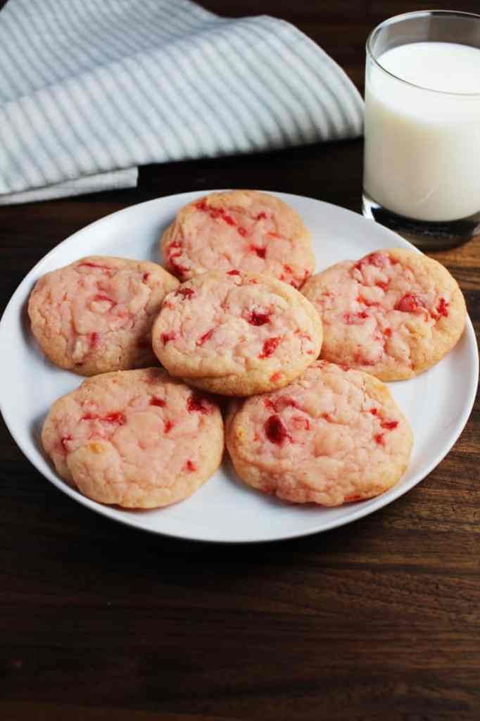 Cherry almond sugar cookies on a plate with a glass of milk