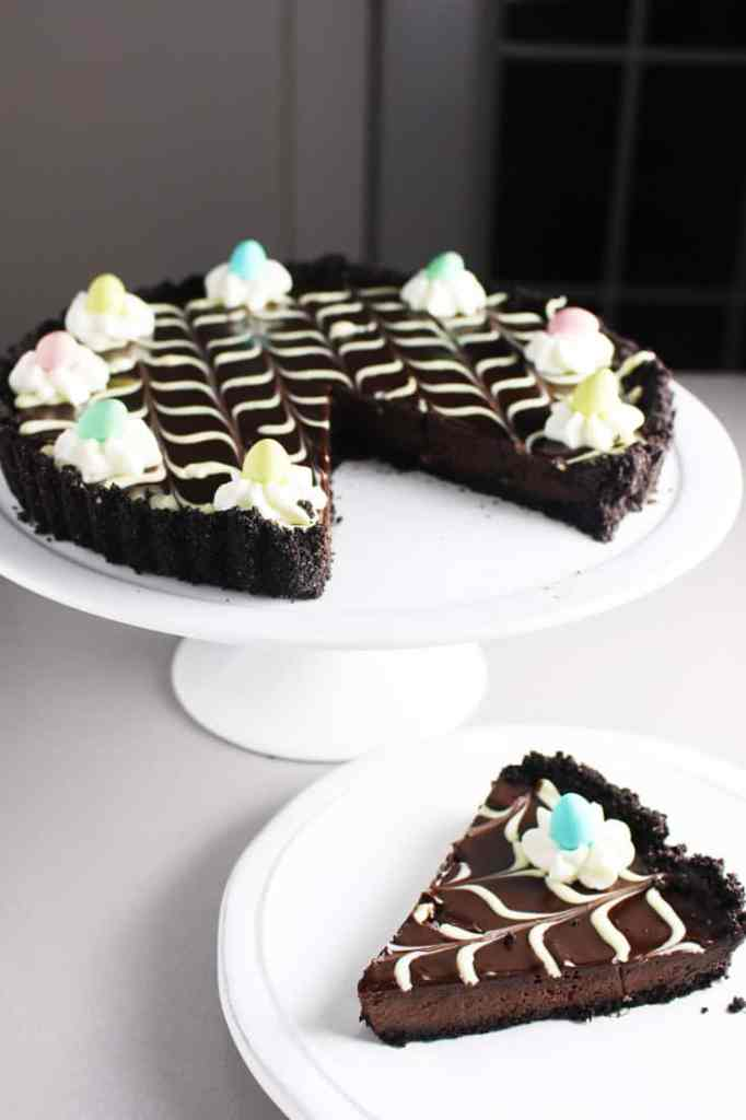 Slice of chocolate tart recipe decorated with Easter mini eggs on a plate with tart on a pedestal in background