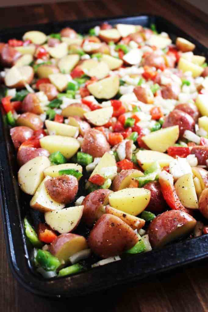 Potatoes, peppers and onions on a baking sheet ready to be roasted for cheesy breakfast potatoes