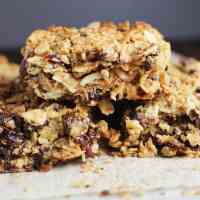 Chewy granola bars stacked on a sheet of parchment paper