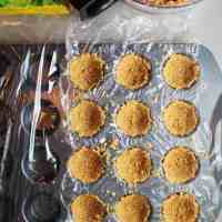 Mini muffin tin lined with plastic wrap being filled with graham cracker crumbs to make tart shells for mini cheesecake tarts