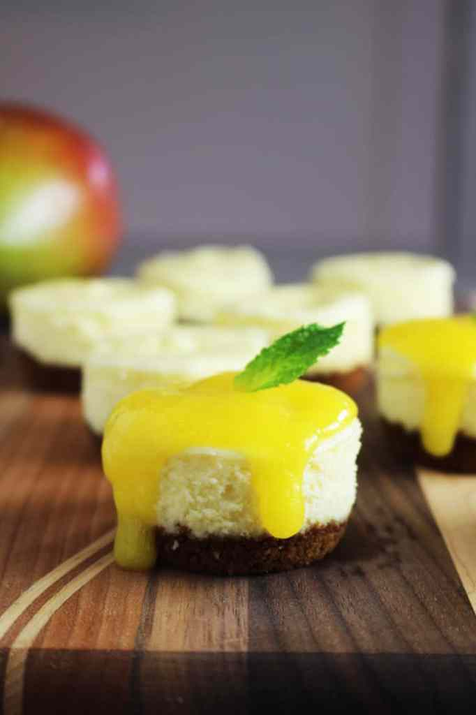 Mini cheesecakes with mango and biscoff crust on a wooden board