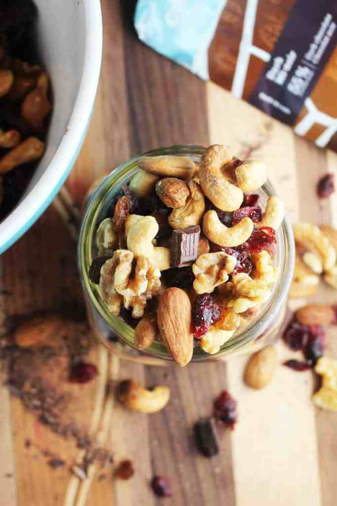 Healthy trail mix in a jar on a wooden board