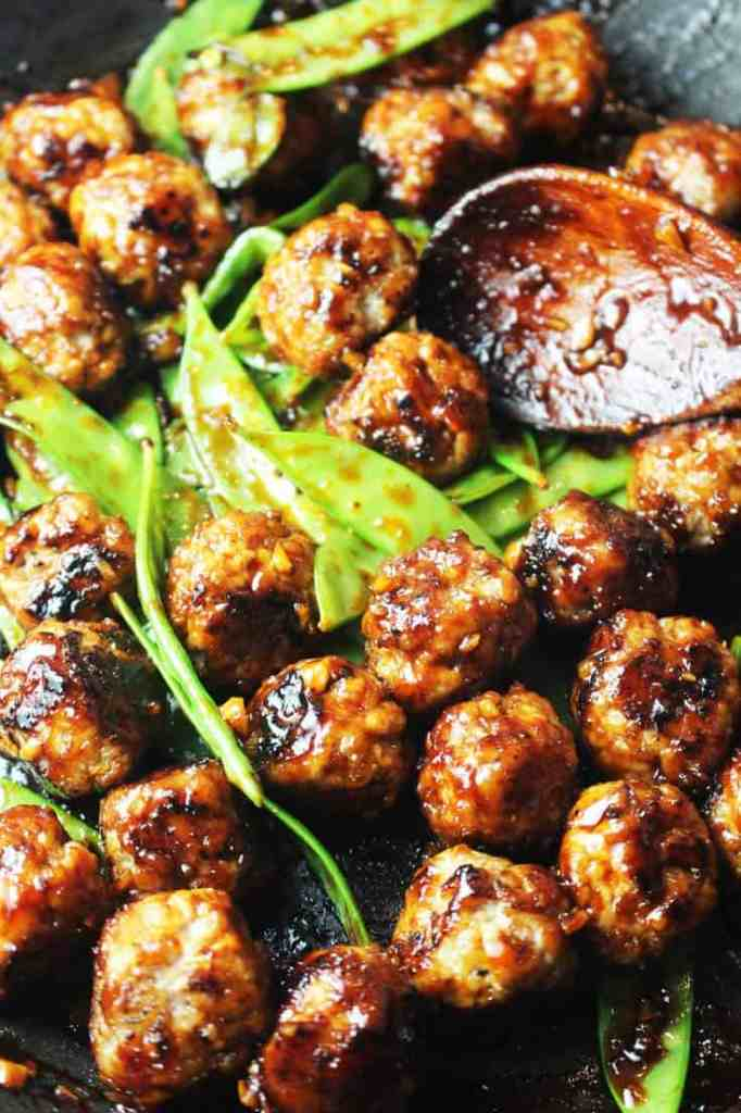 Asian meatballs with snow peas in a pan