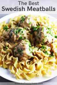 Swedish meatballs over egg noodles on a plate.