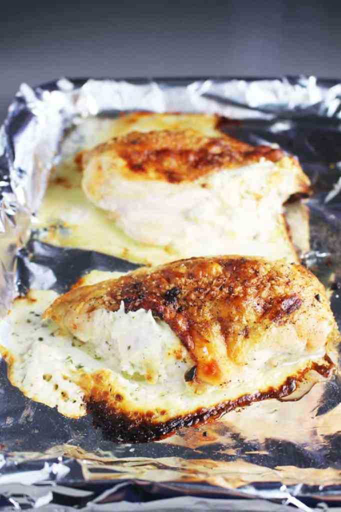 Roasted chicken breasts stuffed with Boursin on a pan lined with aluminum foil