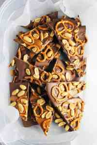 sweet and salty chocolate bark with caramel, peanuts and pretzels in a plastic container with wax paper