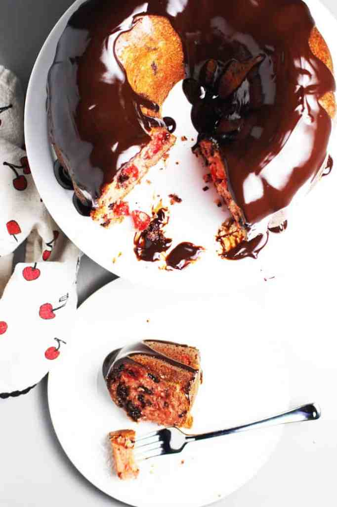 Cherry chocolate cake on a cake stand with a piece of cake on a plate