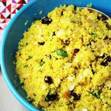 curried couscous salad in a blue serving bowl