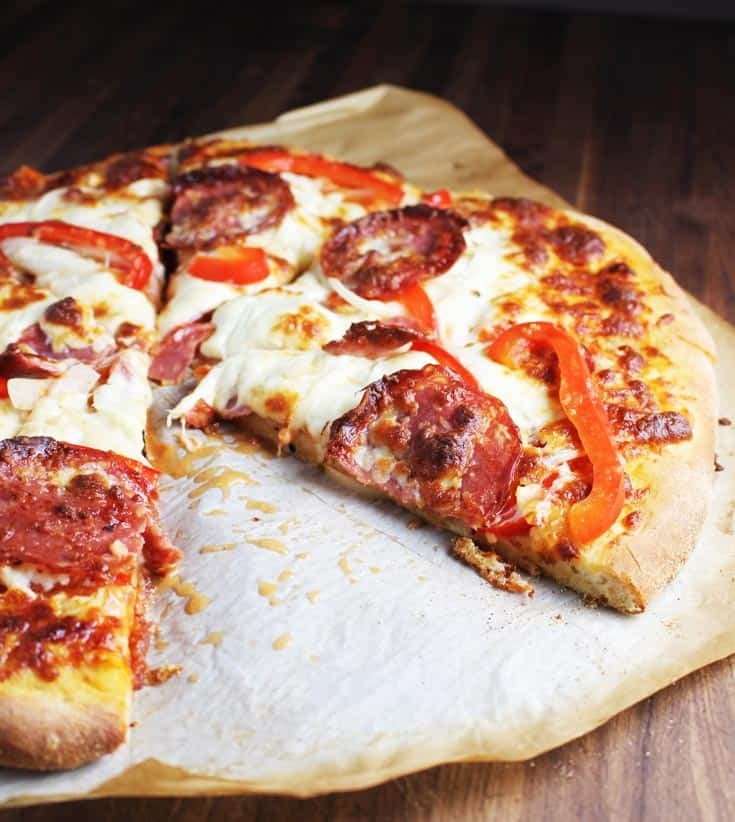 Sliced pepperoni pizza on a piece of parchment paper