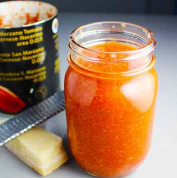 Pizza sauce in a mason jar with parmesan cheese, a microplane grater, and a can of tomatoes in the background