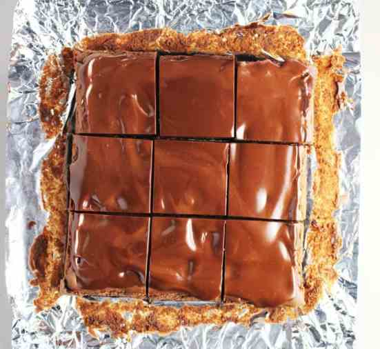 Triple chocolate cheesecake bars just sliced, on top of a sheet of aluminum foil