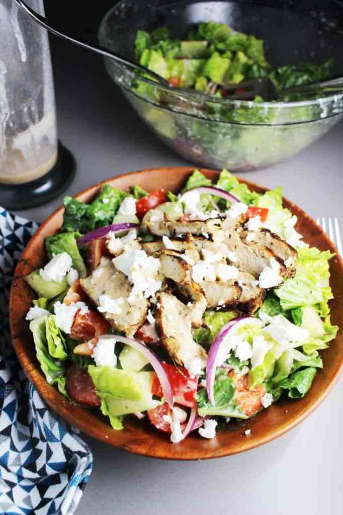 Greek chicken salad in a wooden bowl