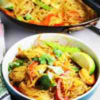 Singapore curry noodles in a bowl garnished with a slice of lime and cilantro