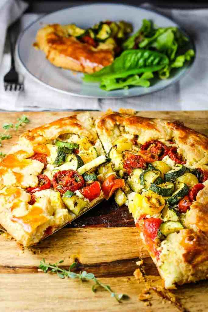 A rustic zucchini tomato tart on a wooden board with a slice take out