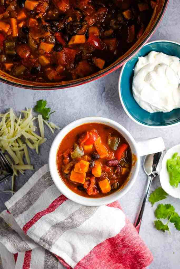 A bowl of vegetarian sweet potato chili with sour cream, grated cheese and cilantro on the side