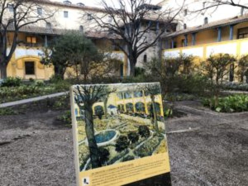 Easel showing Vincent's painting of his hosptial's gardens, and the actual gardens where he created this painting