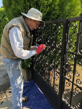 Jeff painting outside black metal gate Staying home in Carcassonne