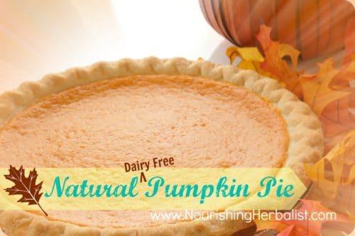 A whole pumpkin pie wihth autumn leaves and a decorative pumpkin