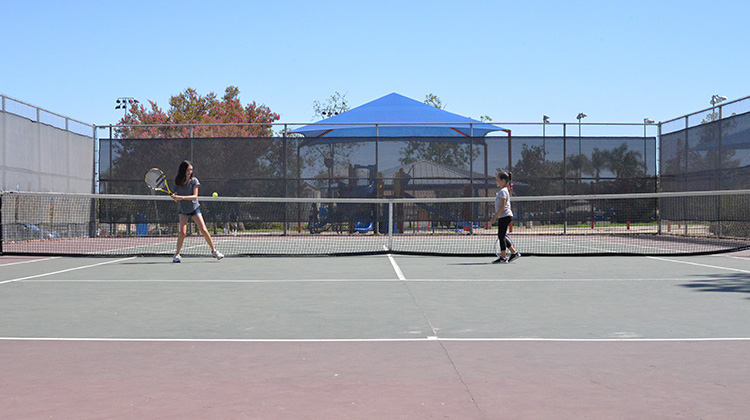 7 and 11 year old kids playing tennis
